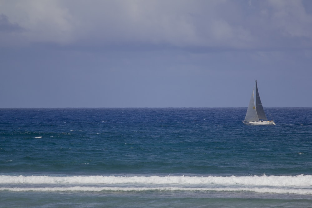 gray sailboat on body of water