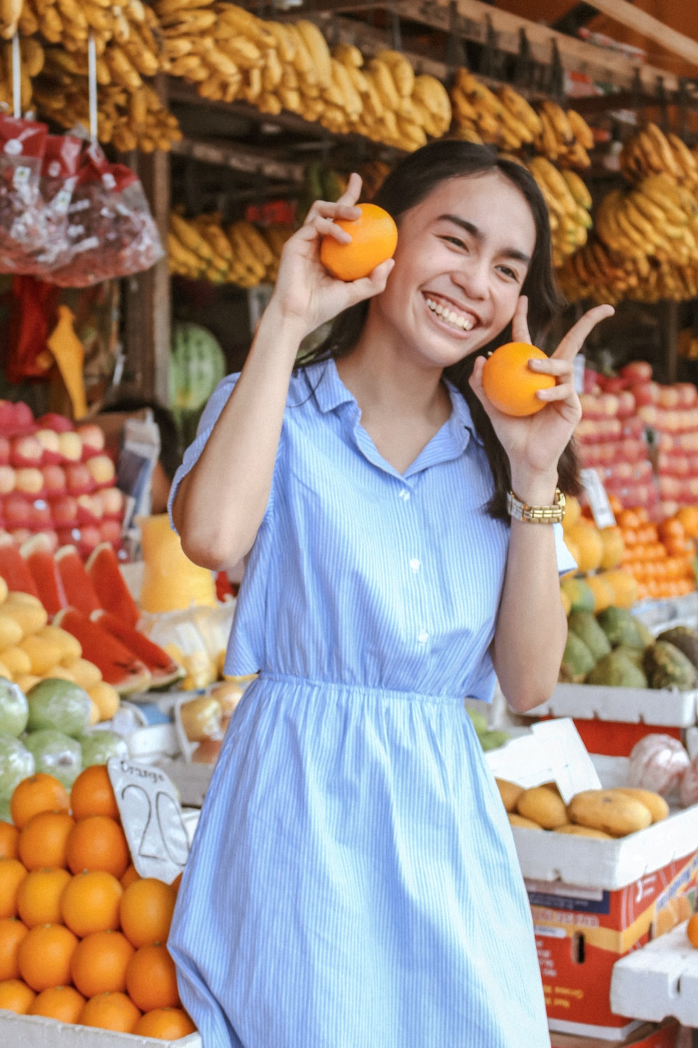 woman standing near lot of fruits