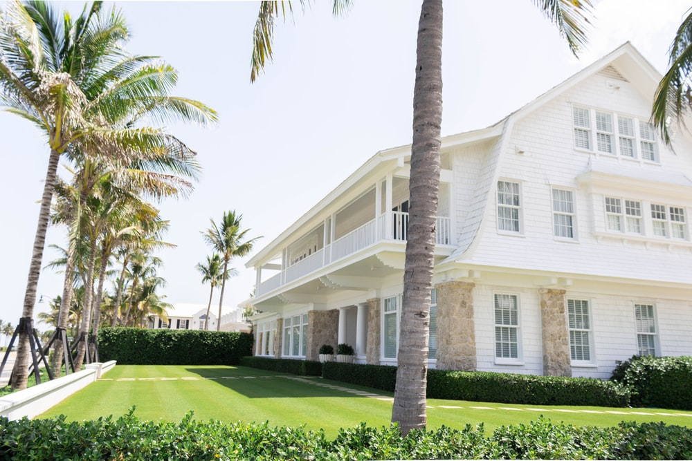 white wooden house near palm trees