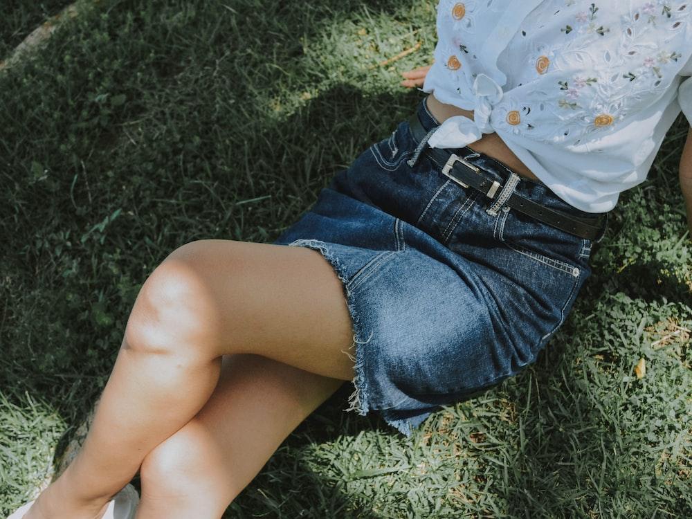 woman wearing blue denim skirt sitting on grasses