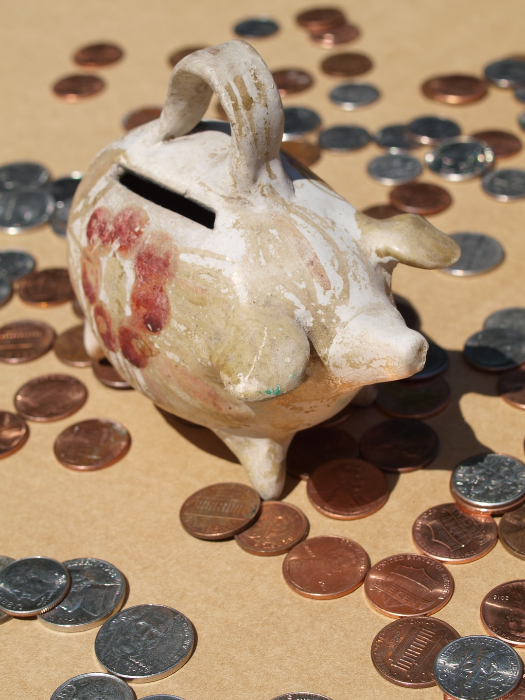 Vintage 1960s potter piggy bank from South America with scattered American coins on a brown background.