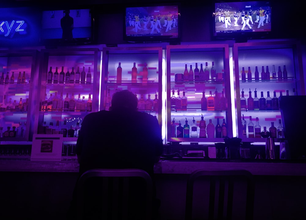 person sitting beside bar counter