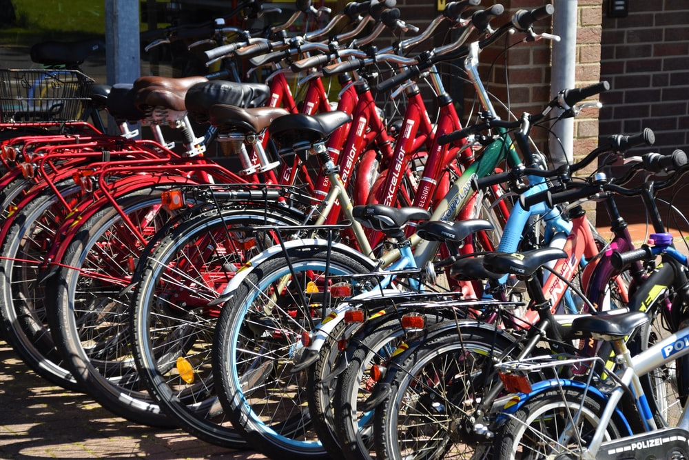 lined red, blue, and black bicycles on display