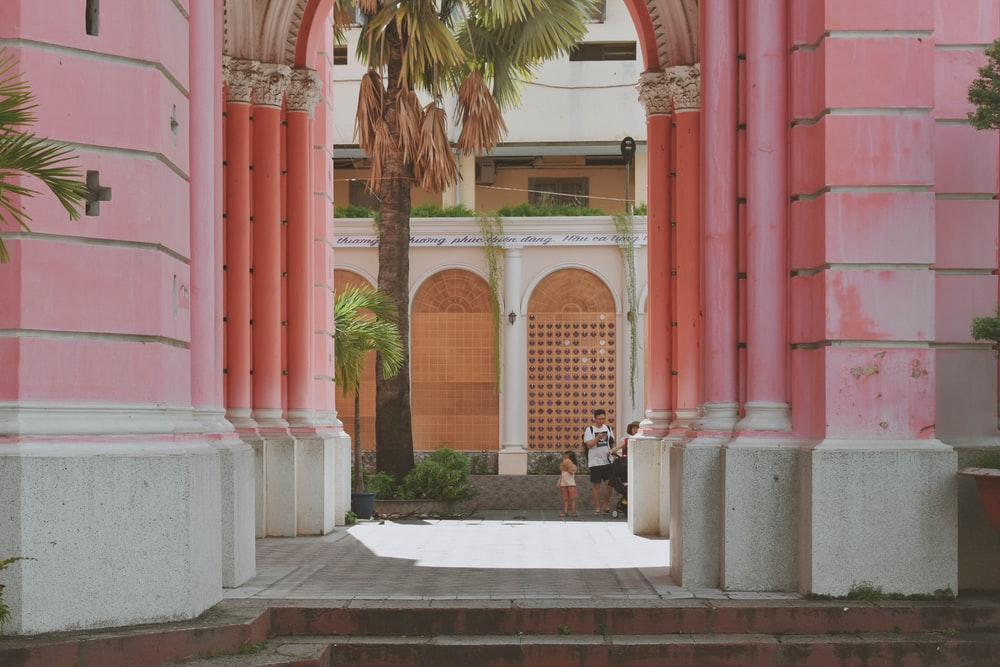 pink concrete building with arch walkway