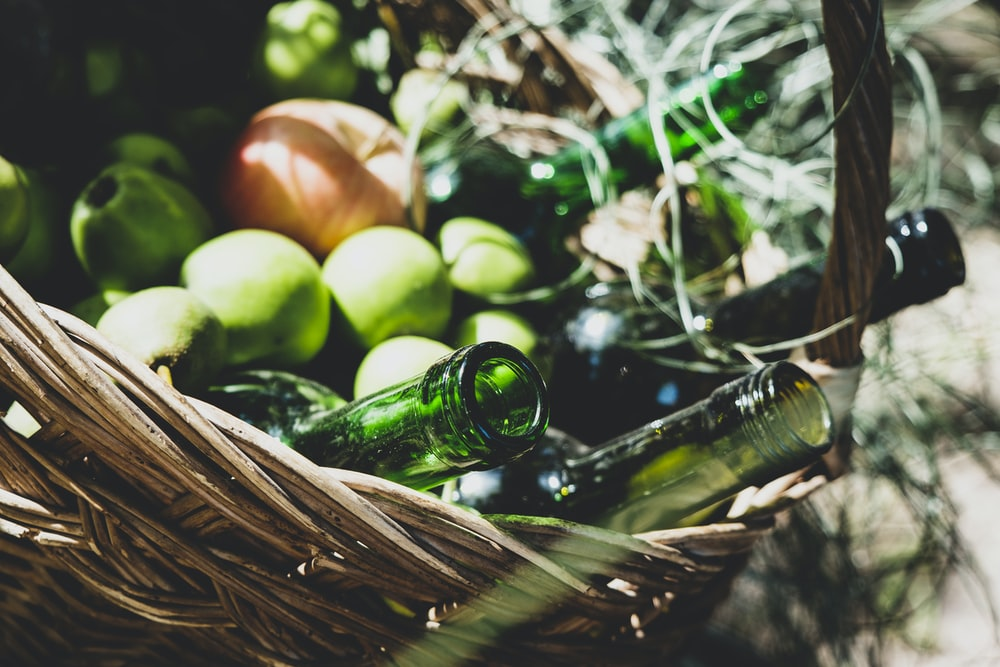 green mango fruits near empty bottles on brown wicker basket