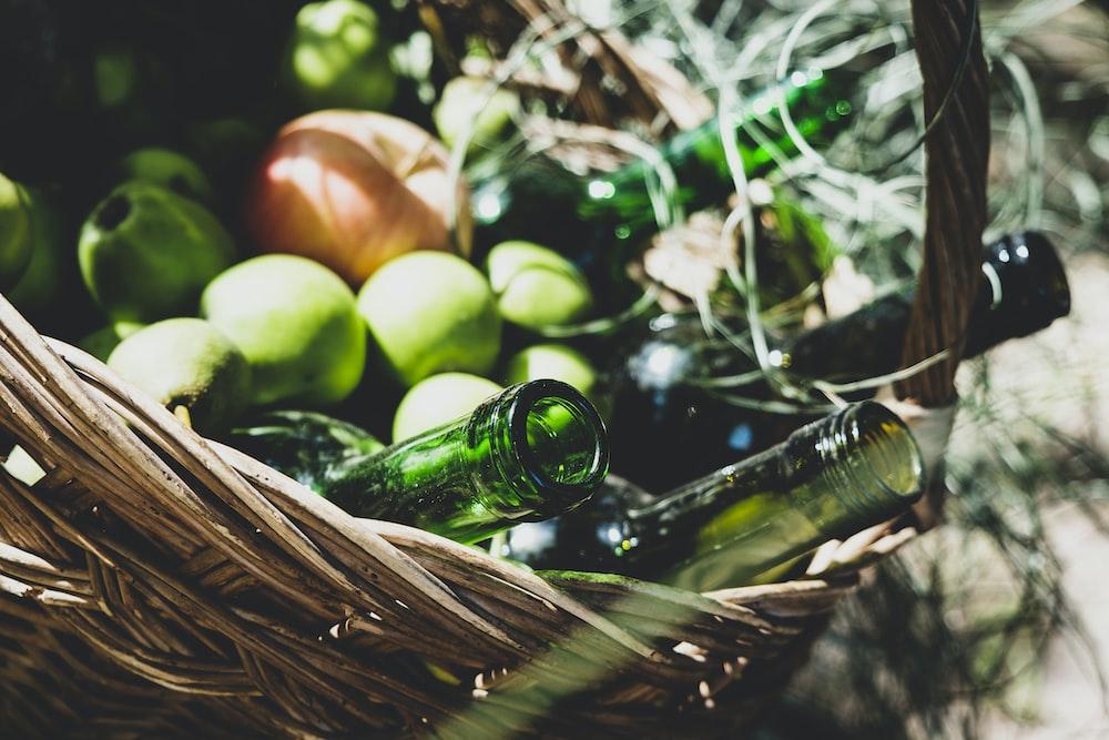 green mango fruits near empty bottles on brown wicker basket
