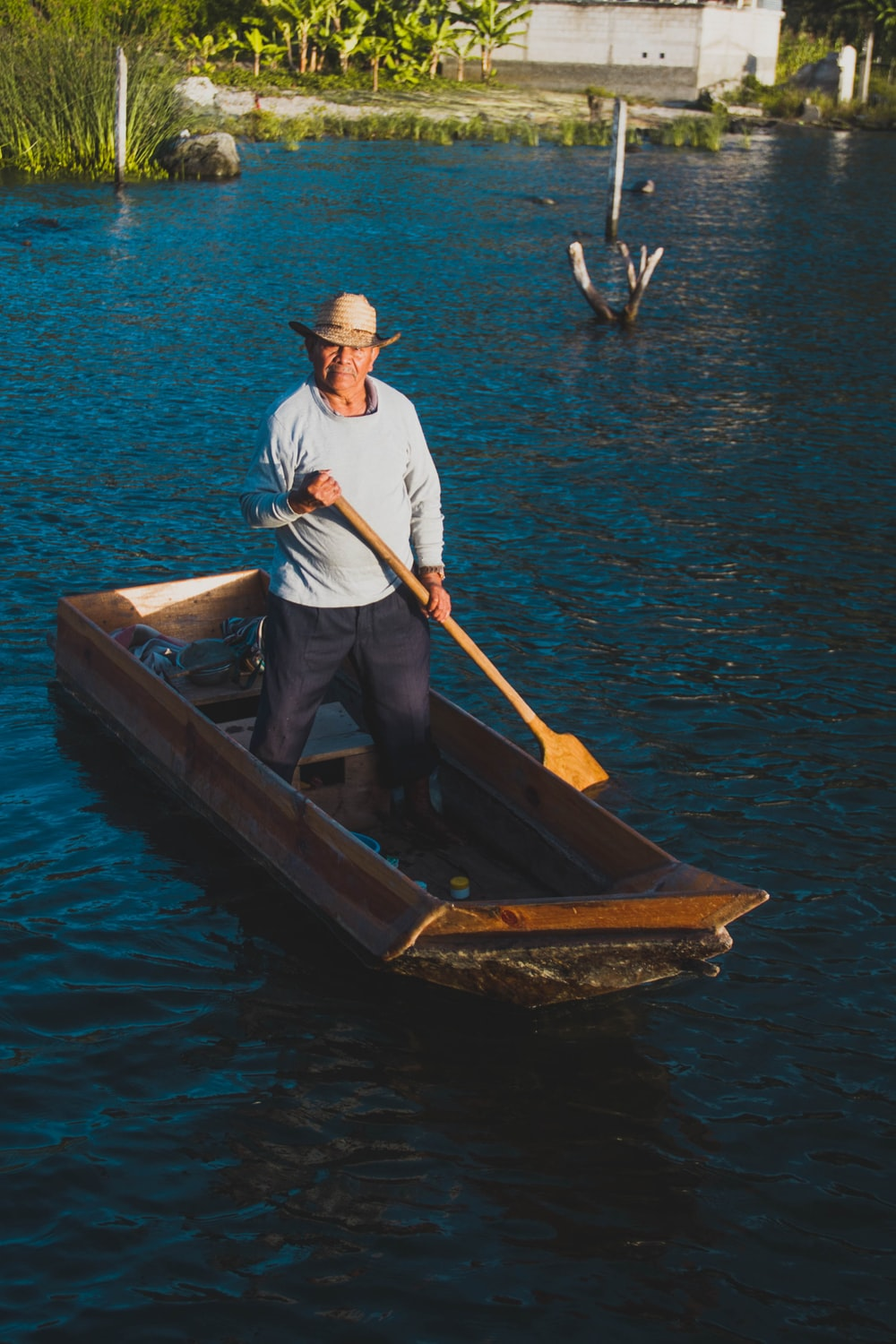 man riding on brown row boat during daytime