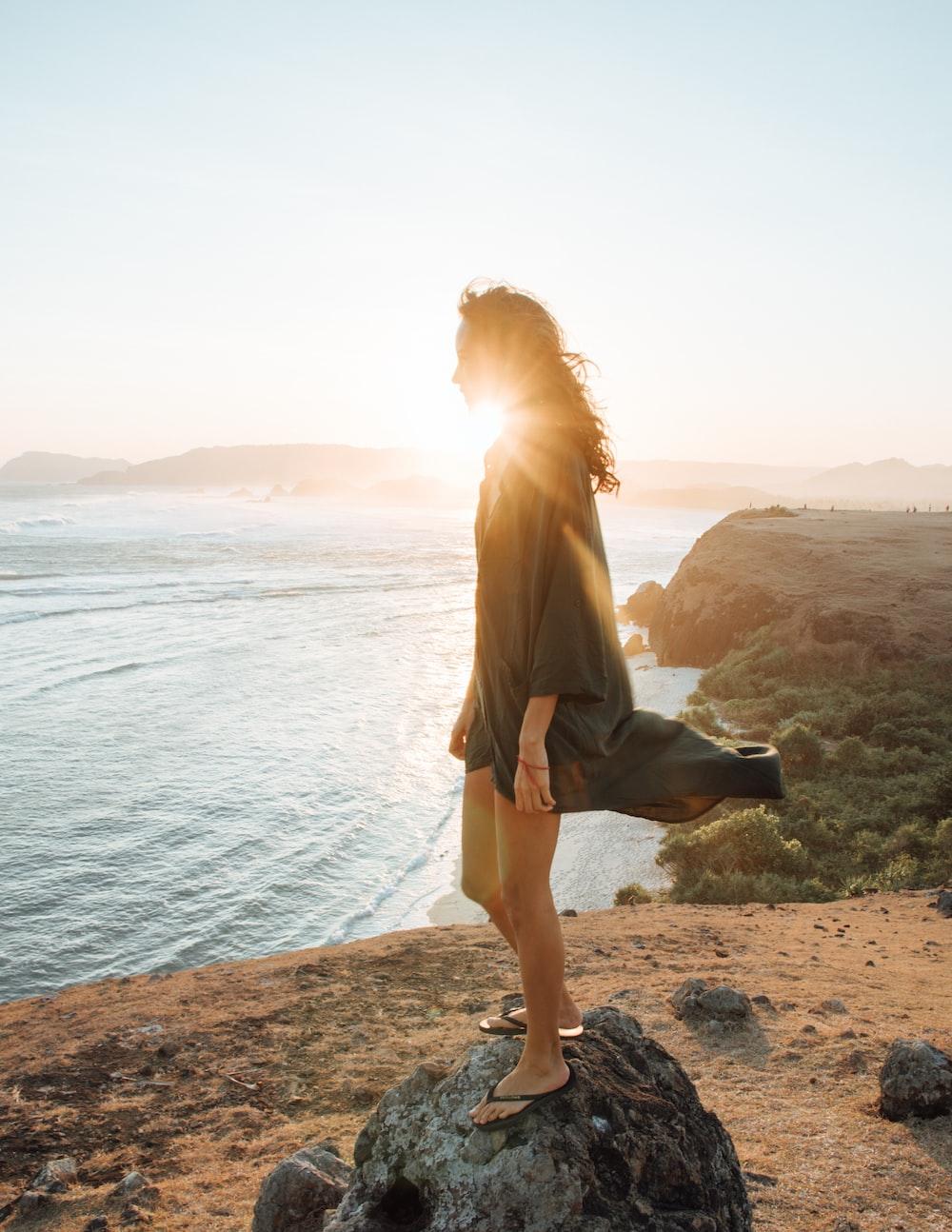 woman wearing black dress standing on rock near body of water