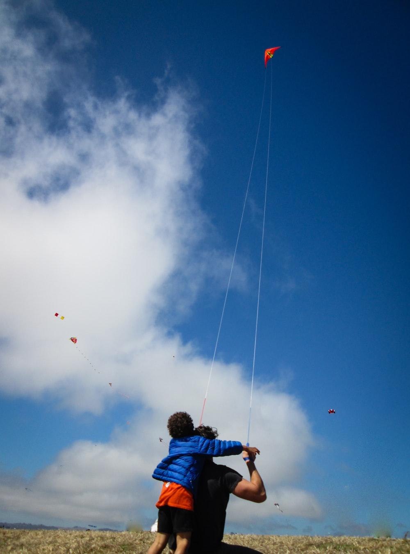 man and boy playing kite during daytime