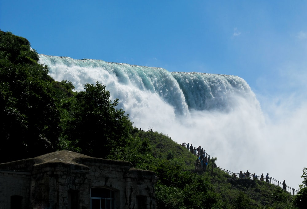 waterfall under blue sky during daytime