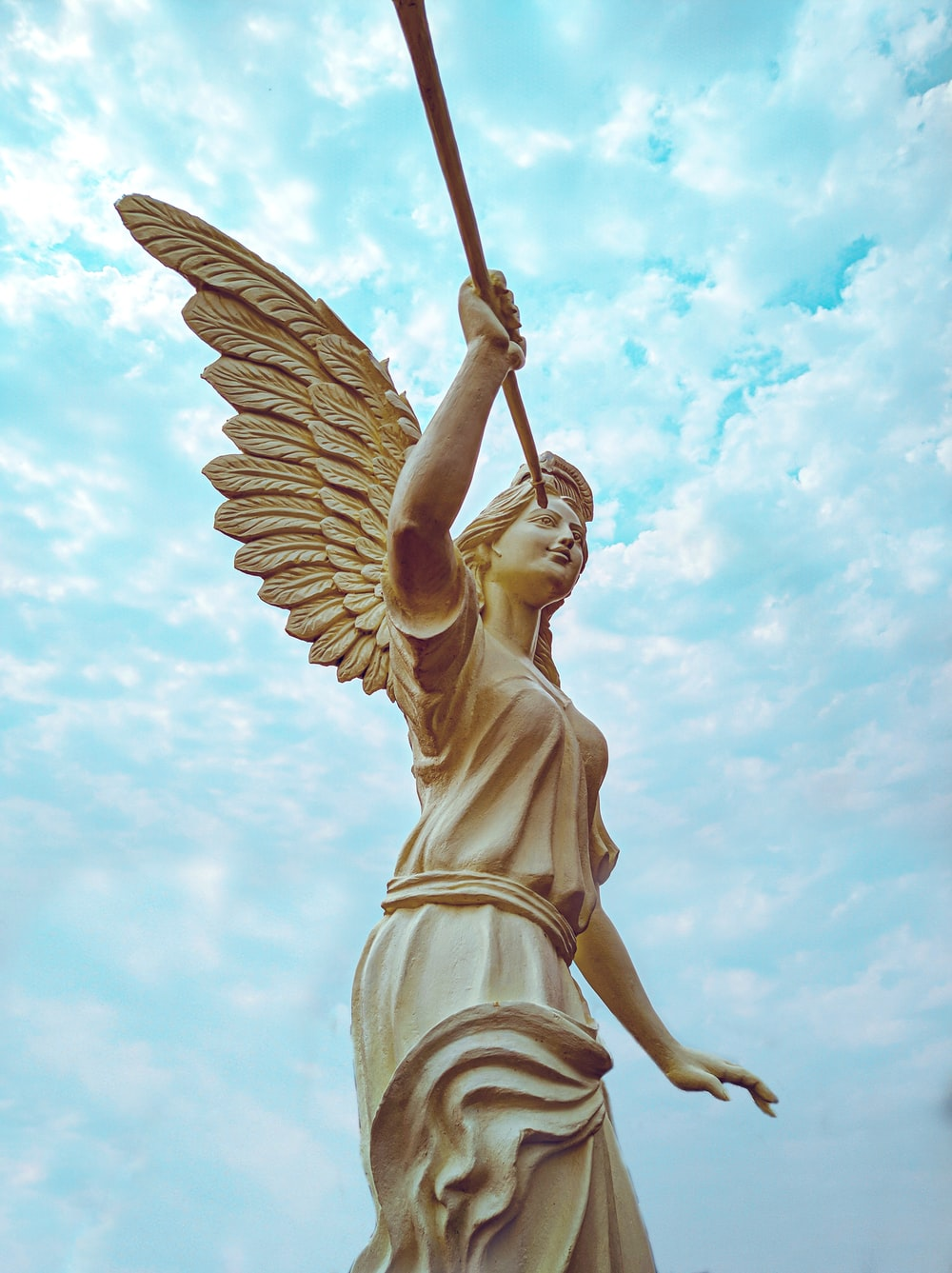 angel statue under white clouds and blue sky during daytime