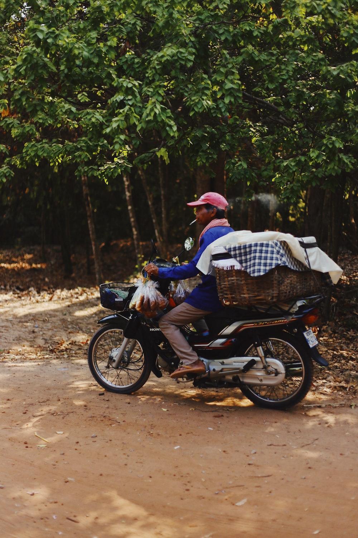 man riding black motor scooter