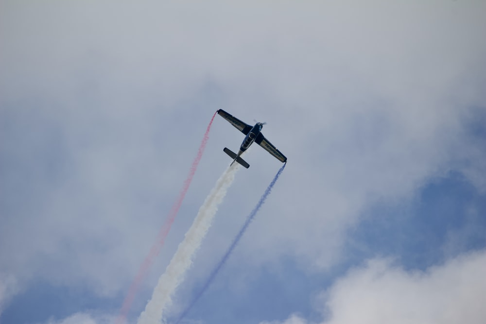 black airplane flying below gray clouds during daytime