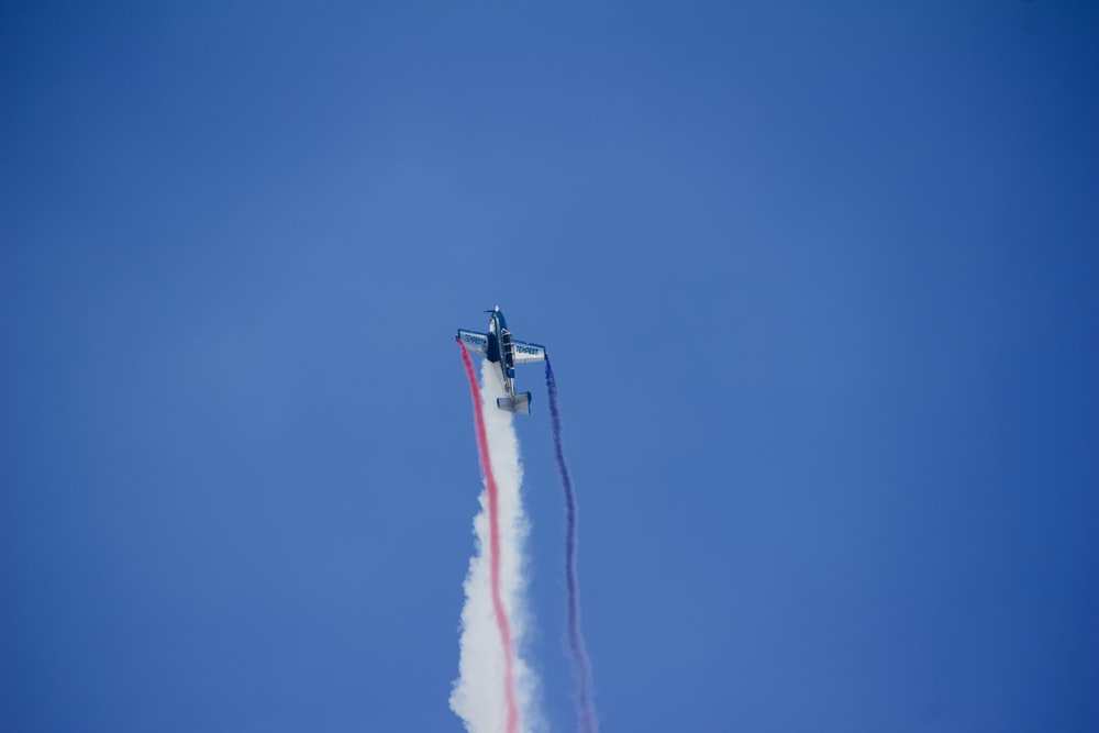 airplane flying upwards with red, white, and blue contrails