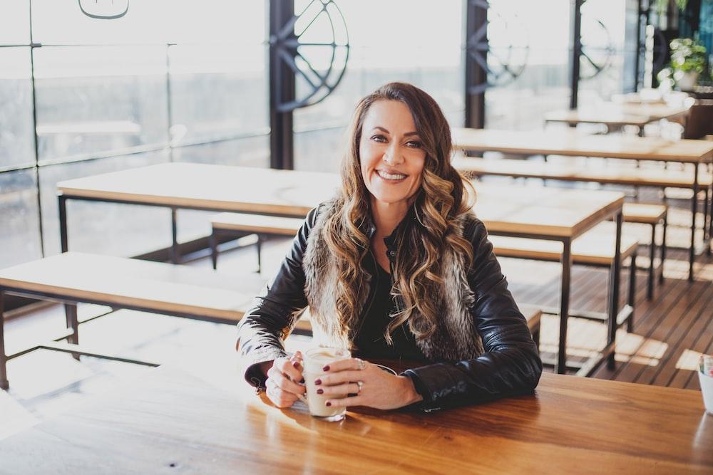smiling woman wearing jacket sitting beside table