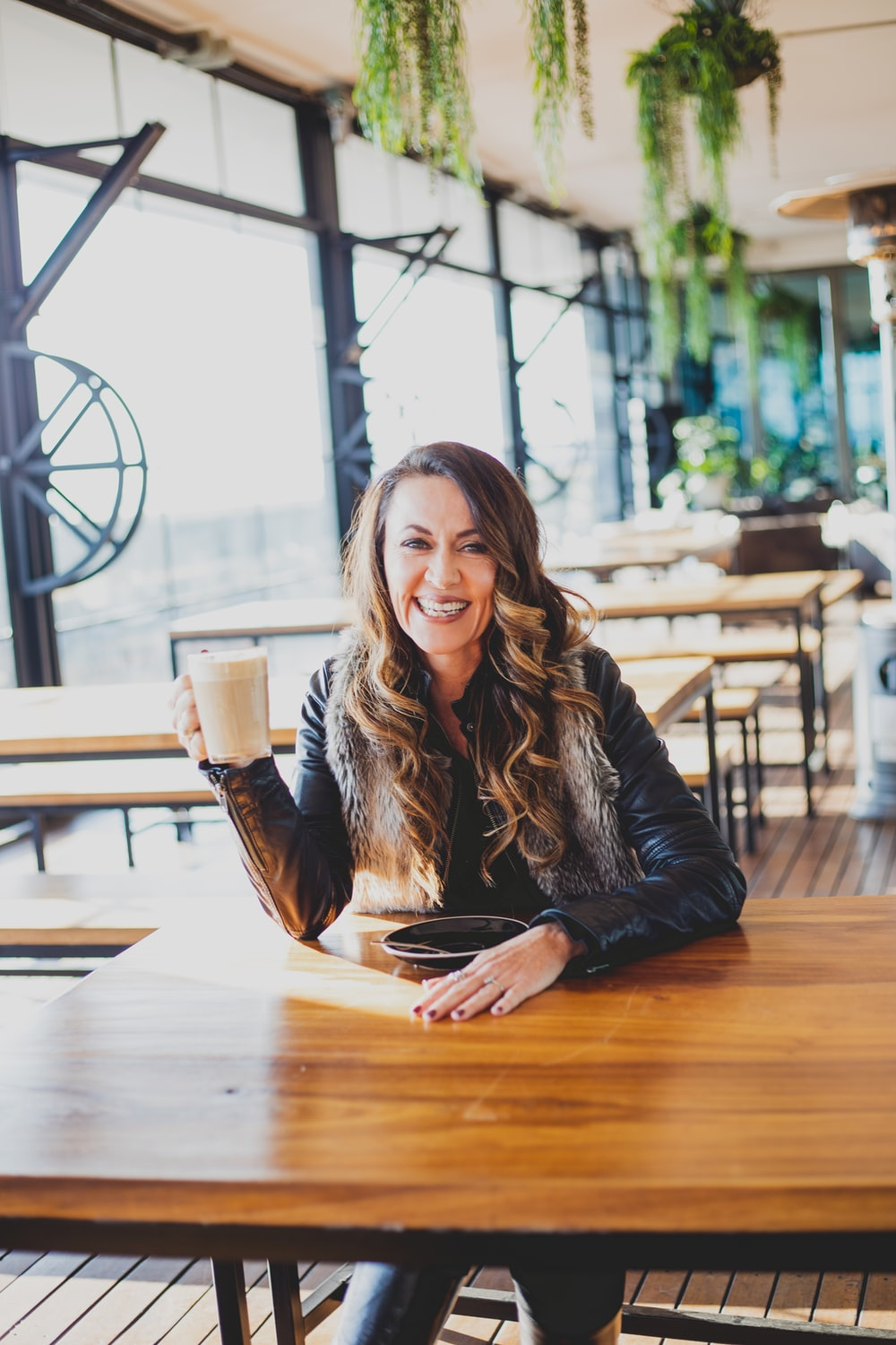 woman smiling and sitting beside table inside eatery