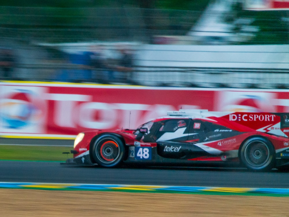 red and white sports car on track photo