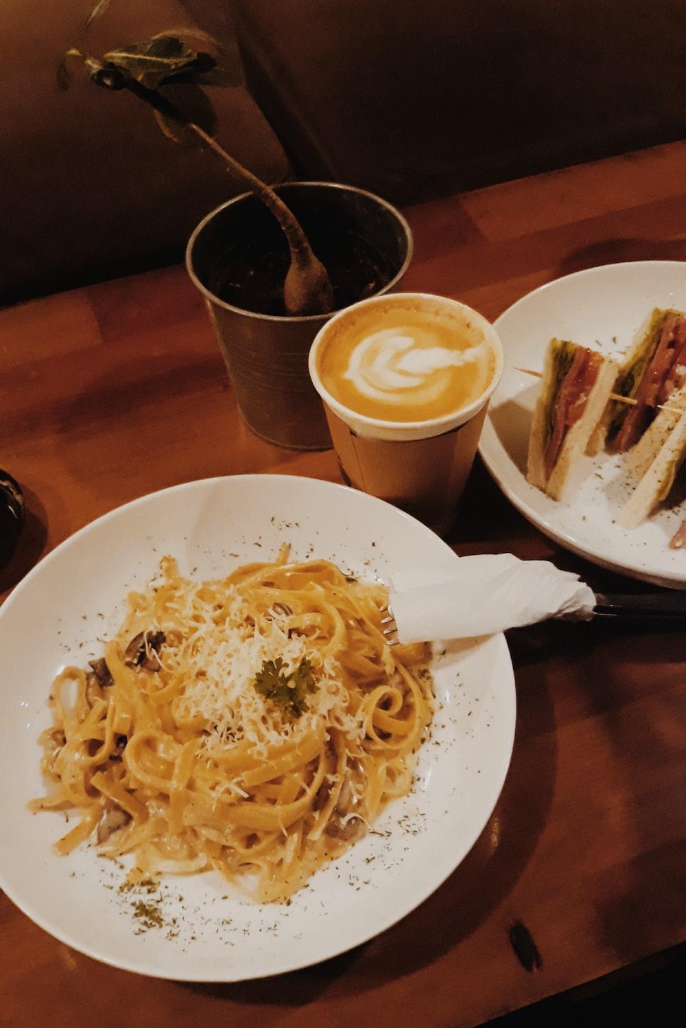 pasta on plate beside latte