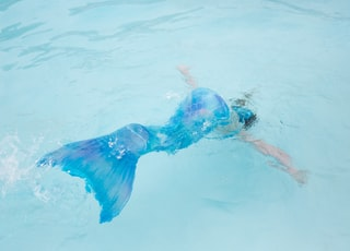 person wearing blue mermaid costume on body of water during daytime