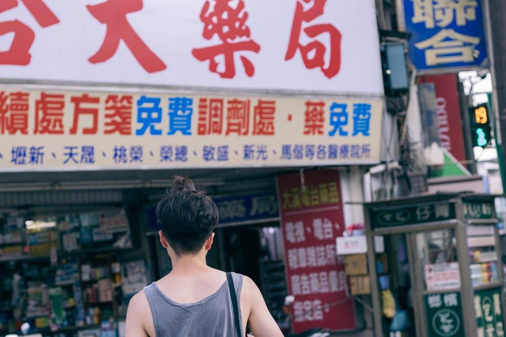 person wearing gray tank top walking on street during daytime