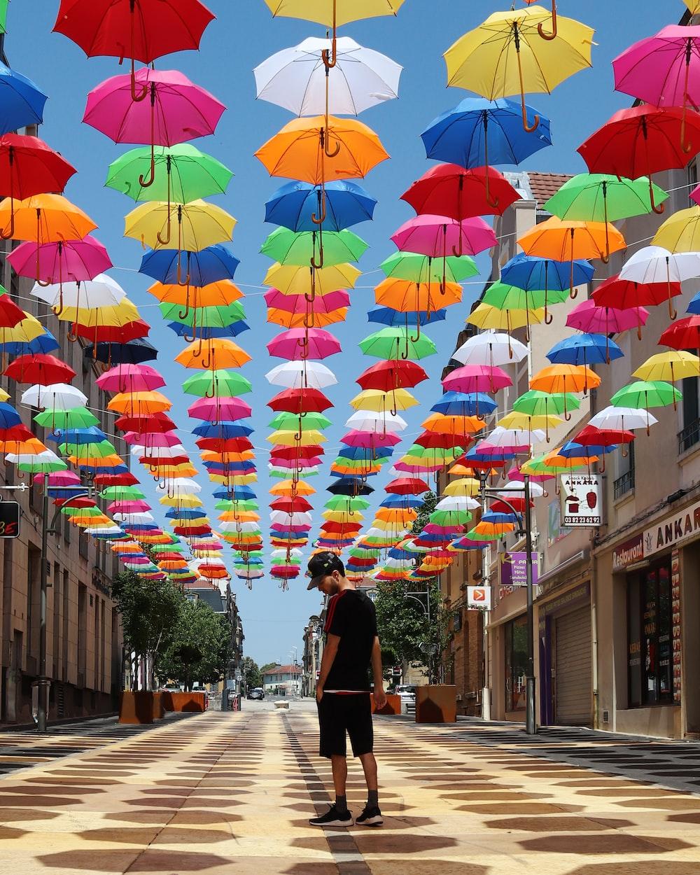 man standing under suspended multicolored umbrellas in street photo – Free Human Image on Unsplash