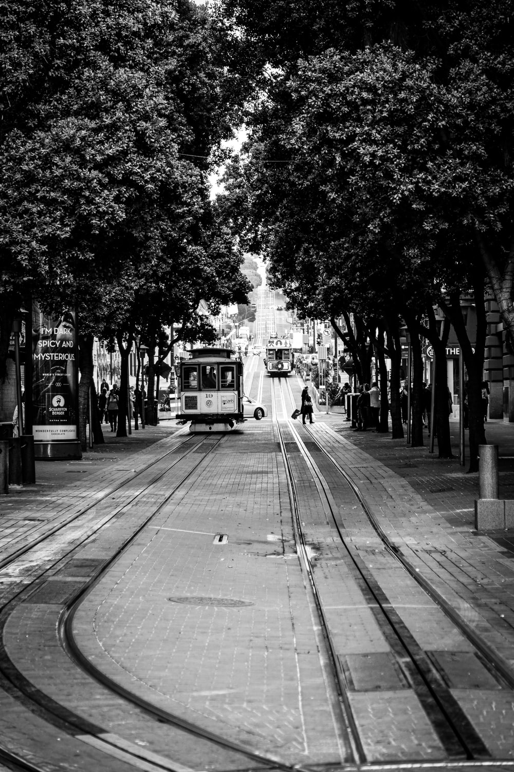grayscale photo of people and tram in street