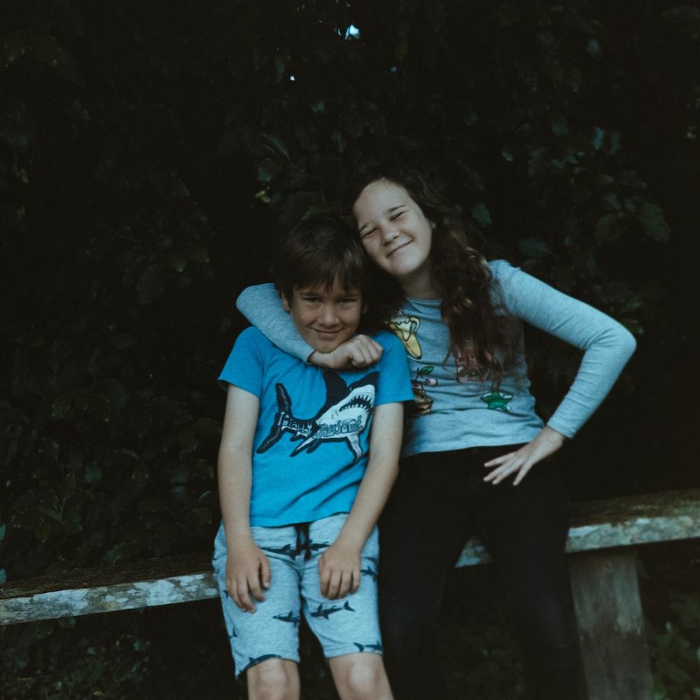 girl hugging boy while sitting on bench