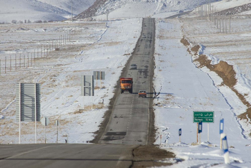 orange truck and car going in opposite directions in straight highway