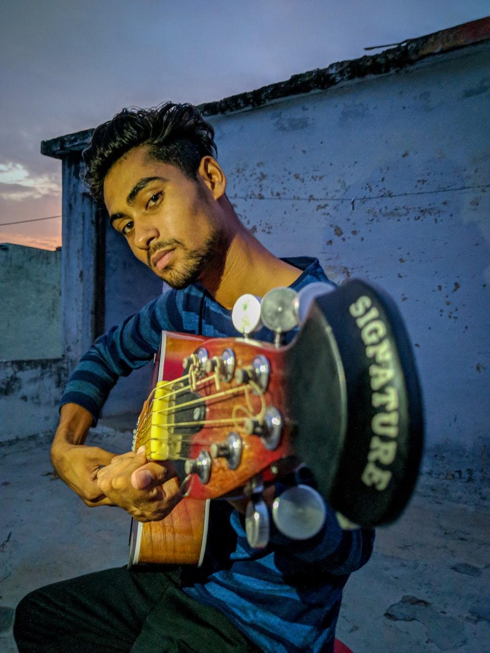 man playing guitar during nighttime