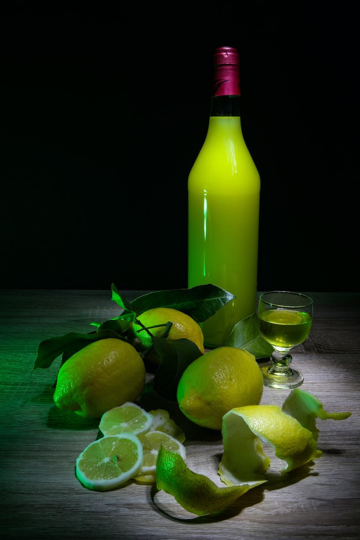 lemon fruits and yellow glass bottle