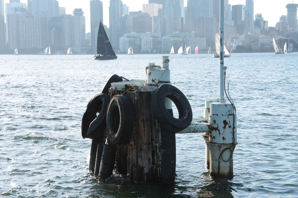 vehicle tires attached to wooden poles at the harbor