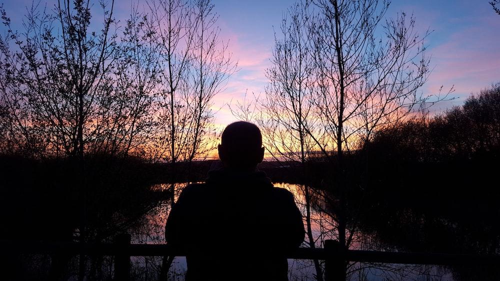 silhouette of man watching orange setting sun in horizon