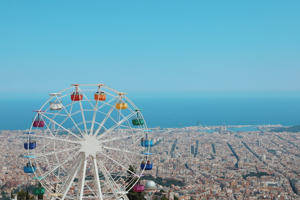 photography of ferris wheel and buildings beside seashore during daytime