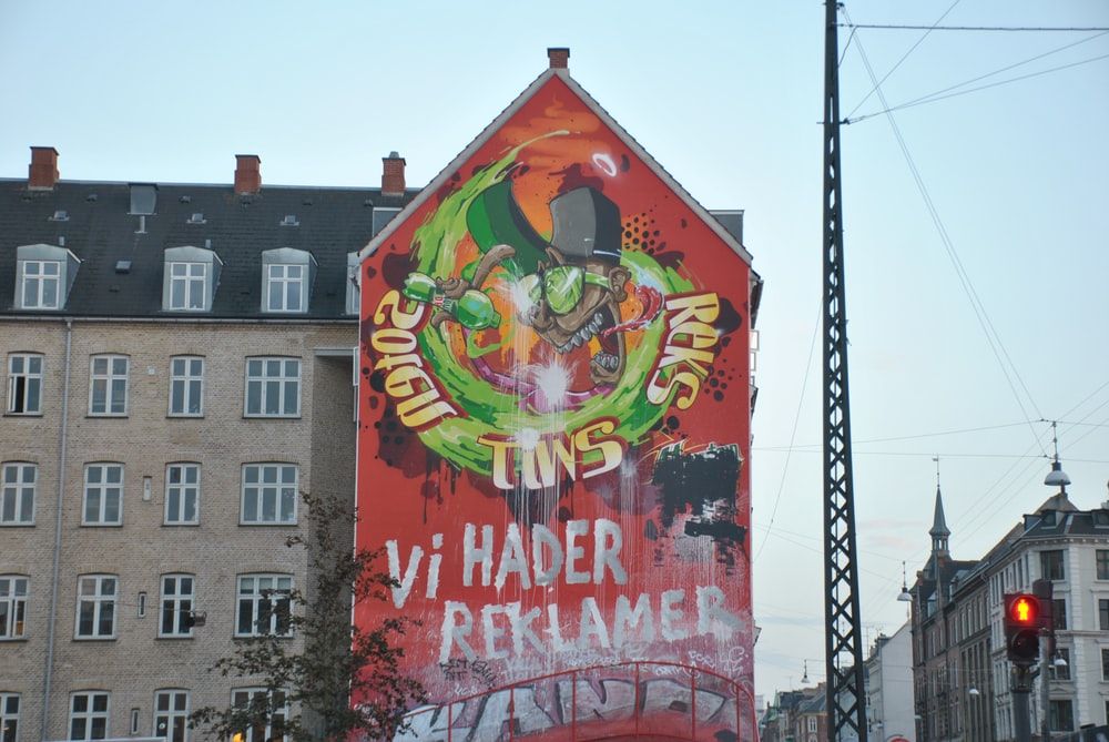 orange and green graffiti covering a building