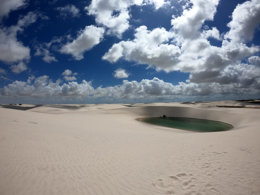 sand dunes with lagoon under cloudy sky