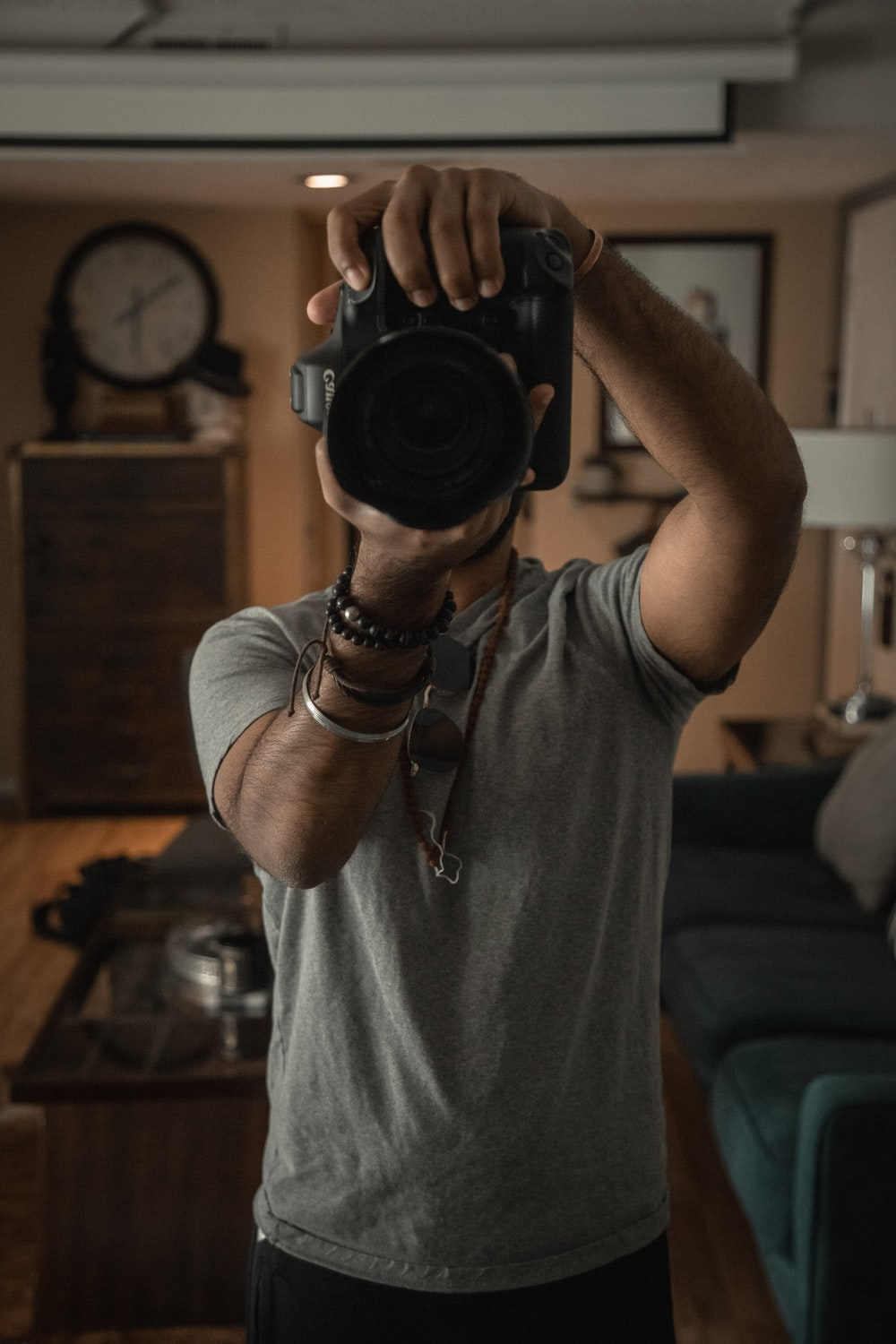 man in grey t-shirt with black DSLR camera