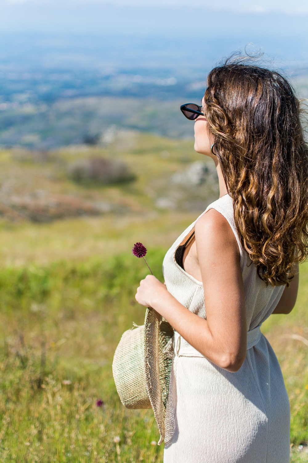 woman standing on green grass near mountain during daytime