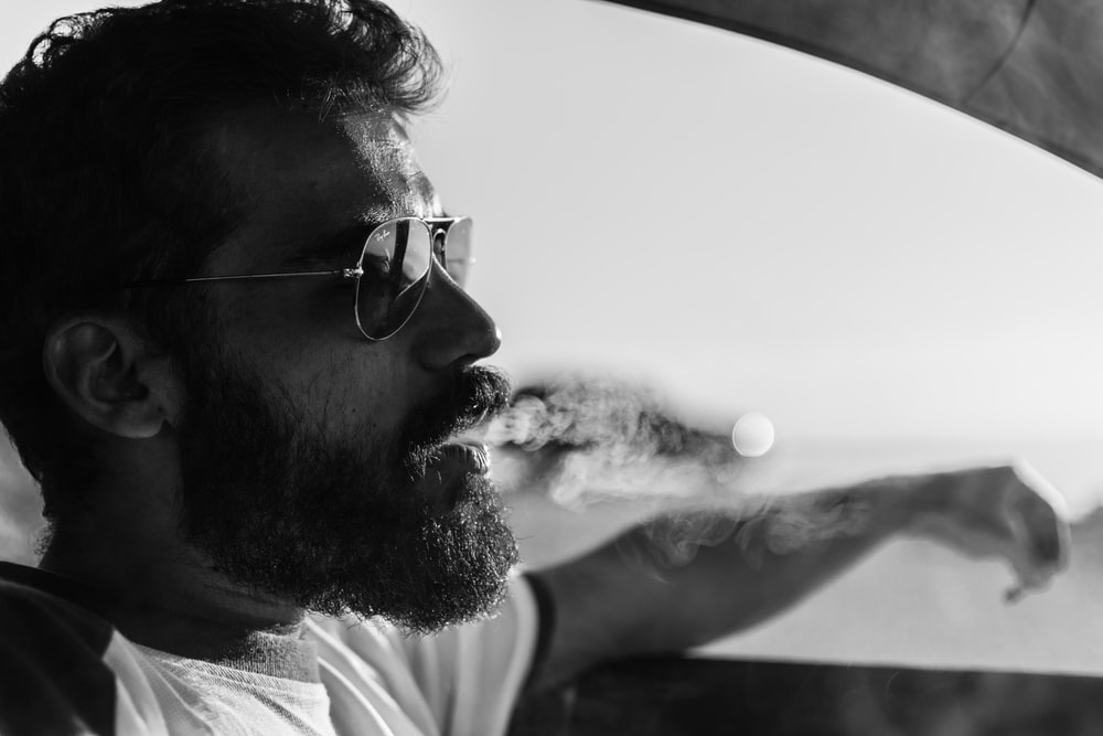 grayscale photography of man inside vehicle