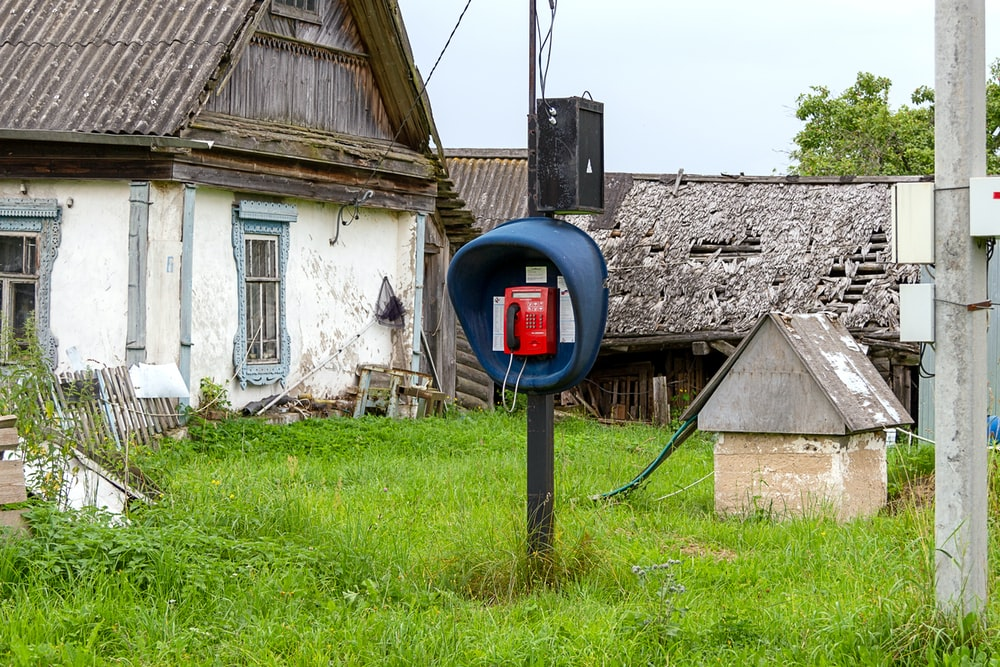 telephone booth near house with attic