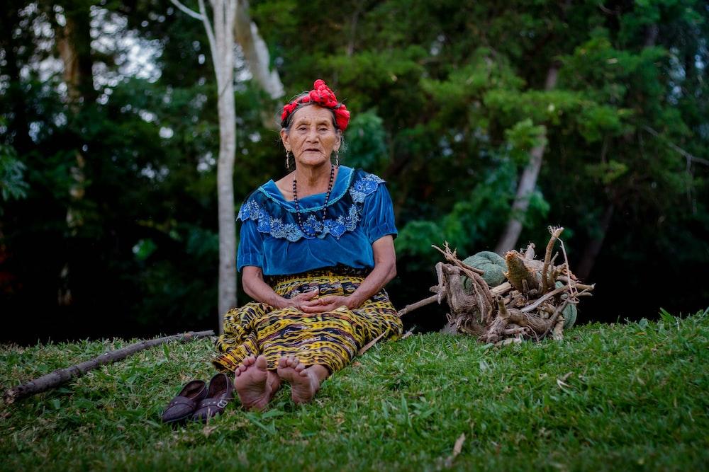 woman sitting on grass near trees