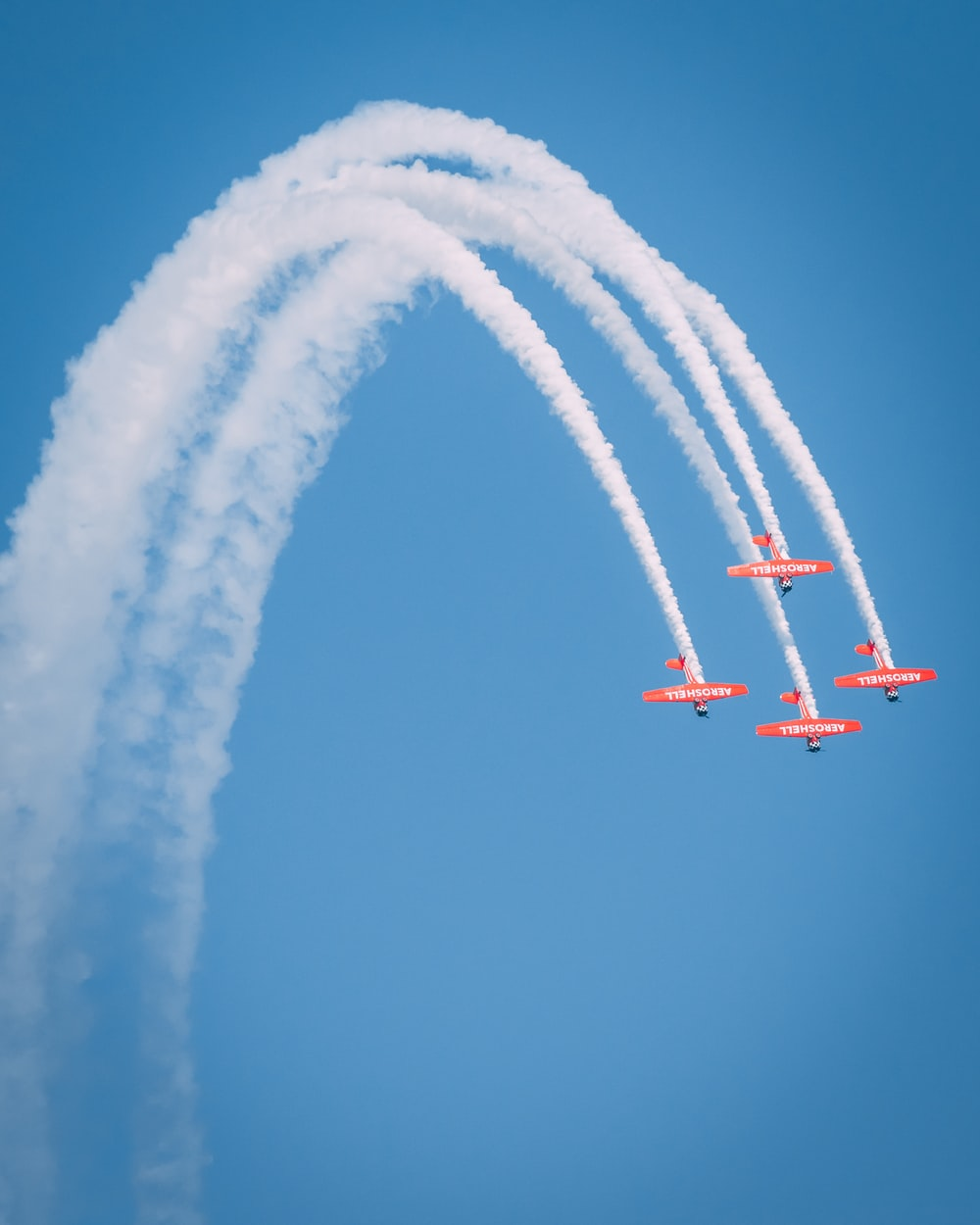 four red-and-white planes under clear blue sky