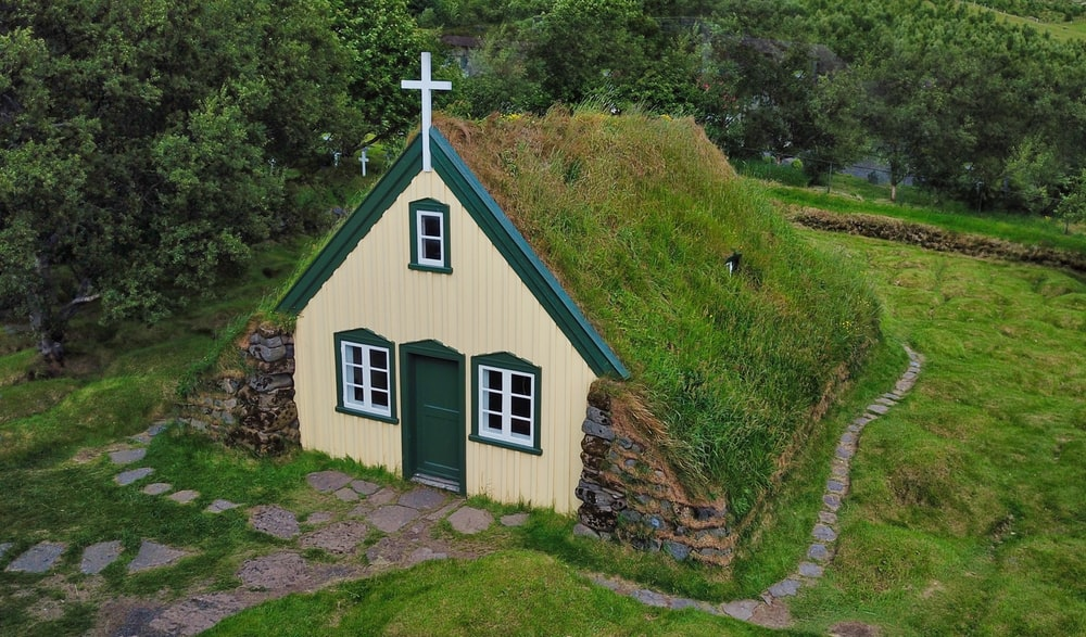 green and white grass roofed church building