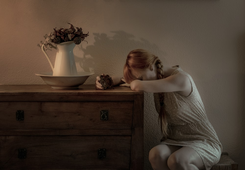 woman sitting beside drawer