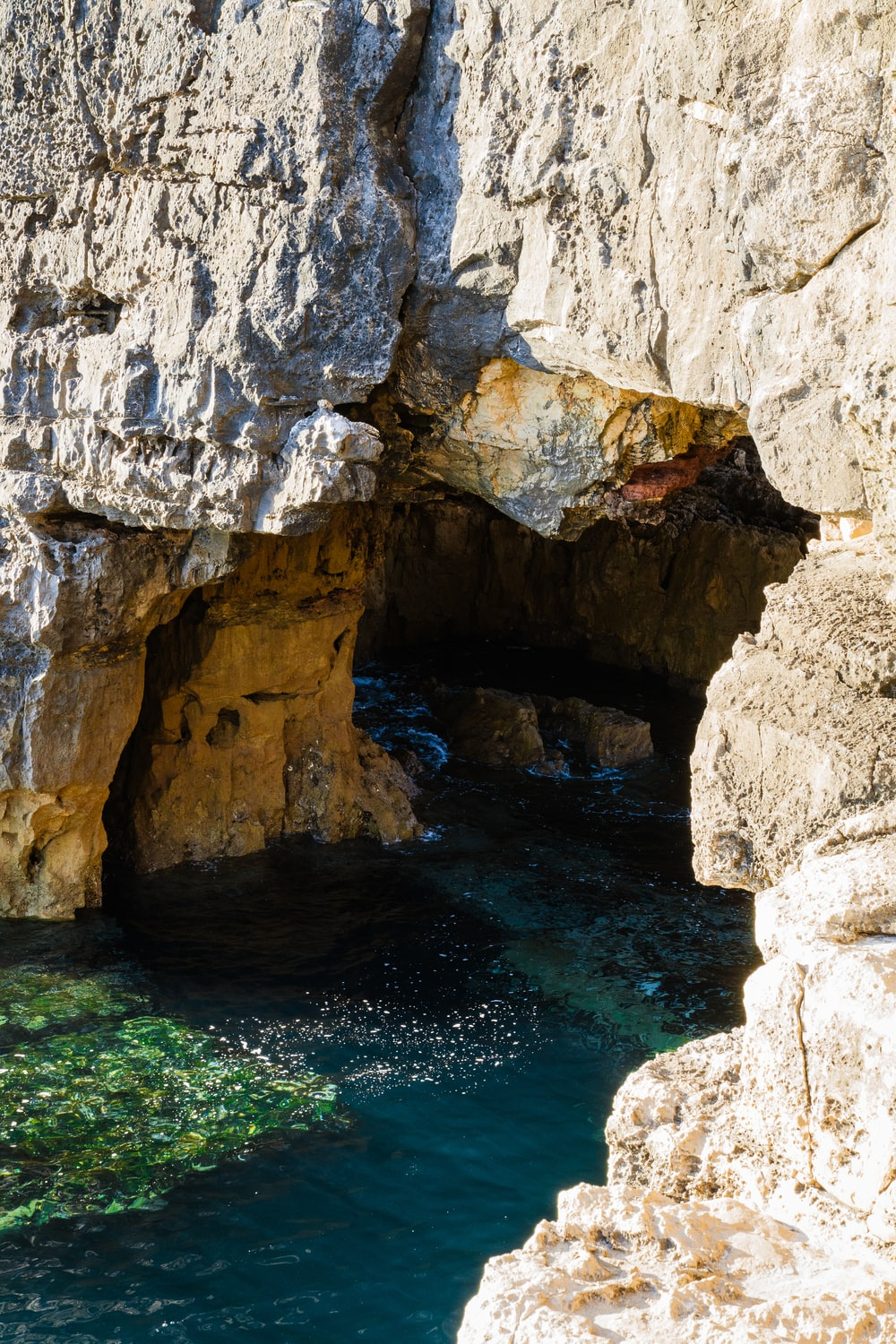 gray cave in body of water