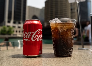 Coca-Cola soda tin can and cup on table close-up photography