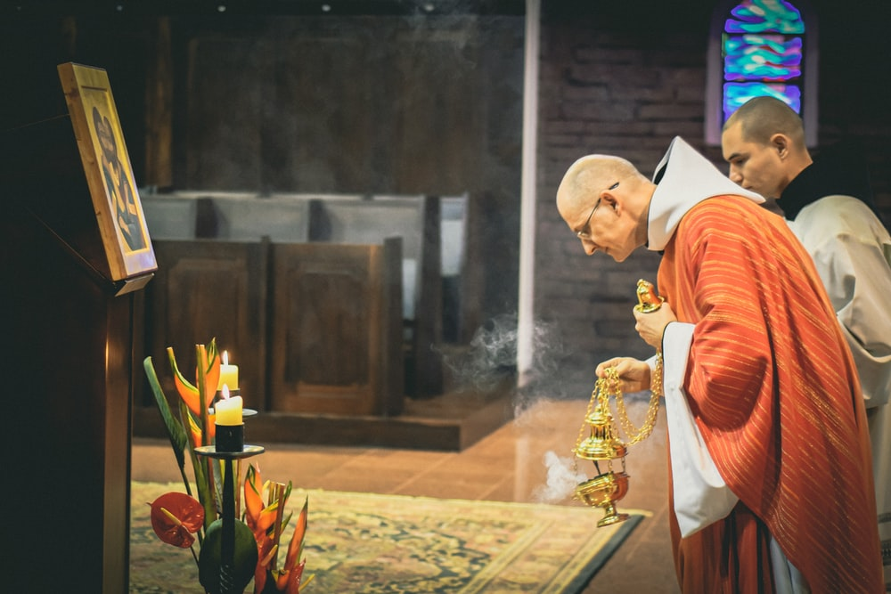 priest holding brass-colored censer