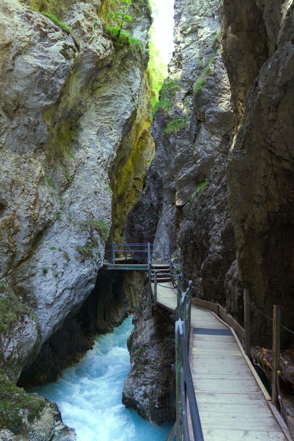 bridge under rock formation during daytime