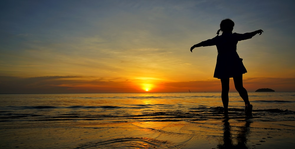 girl standing on seashore during golden hour