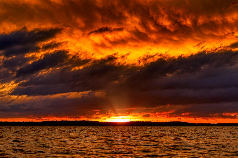 sea under cloudy sky at sun rise