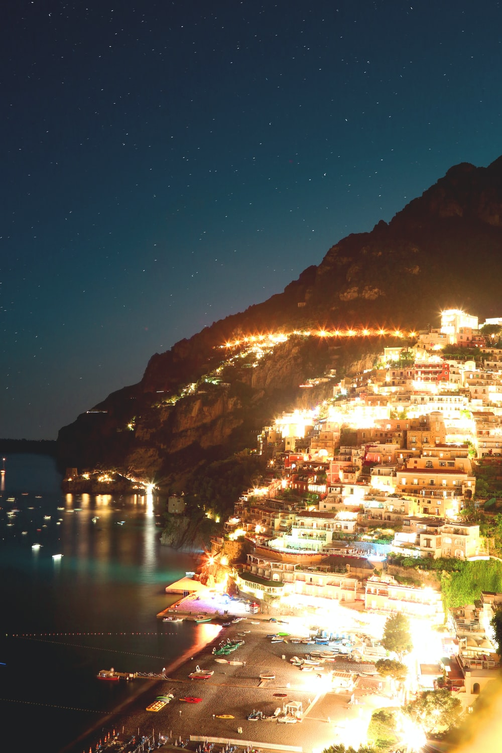 aerial photography of building on mountain beside seashore during nighttime